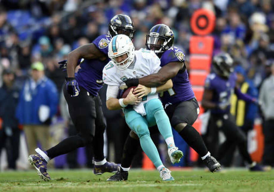 Miami Dolphins quarterback Ryan Tannehill, center, is sacked by Baltimore Ravens linebacker Matt Judon, right, in the second half of an NFL football game, Sunday, Dec. 4, 2016, in Baltimore. (AP Photo/Gail Burton)