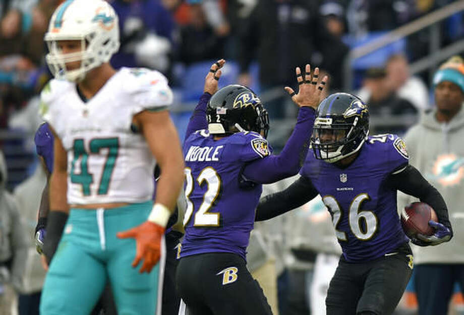Baltimore Ravens defensive back Jerraud Powers, right, celebrates with teammate Eric Weddle after intercepting a pass in the second half of an NFL football game against the Miami Dolphins, Sunday, Dec. 4, 2016, in Baltimore. (AP Photo/Nick Wass)