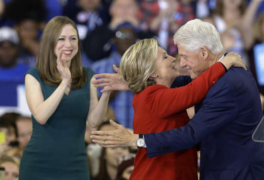 Democratic presidential candidate Hillary Clinton hugs her husband, former President Bill Clinton as their daughter Chelsea Clinton looks on during a campaign rally in Raleigh, N.C., Tuesday, Nov. 8, 2016. (AP Photo/Gerry Broome)