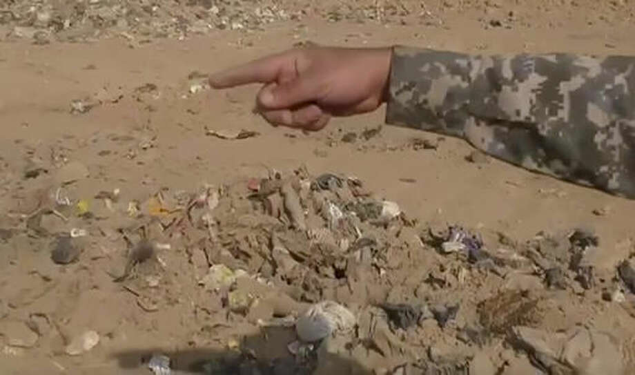 In this Monday, Nov. 7, 2016 frame grab from video, an Iraqi federal police officer points towards a mass grave in Hamam al-Alil, Iraq. Investigators are probing the mass grave that was discovered the previous day by troops advancing further into Islamic State-held territory near the city of Mosul. Associated Press footage from the site shows bones and decomposed bodies among scraps of clothing and plastic bags dug out of the ground by a bulldozer after Iraqi troops noticed the strong smell while advancing into the town of Hamam al-Alil. (AP Photo)