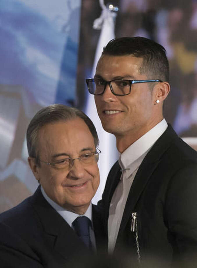 Real Madrid's Cristiano Ronaldo, right and club's President Florentino Perez embrace after signing a new contract at the Santiago Bernabeu stadium in Madrid, Spain, Monday, Nov. 7, 2016. Real Madrid have extend Ronaldo's contract until June 2021, when the three-time world player of the year will be 36. Financial details were not released, although the star forward is expected to remain the team's top-paid player. (AP Photo/Paul White)