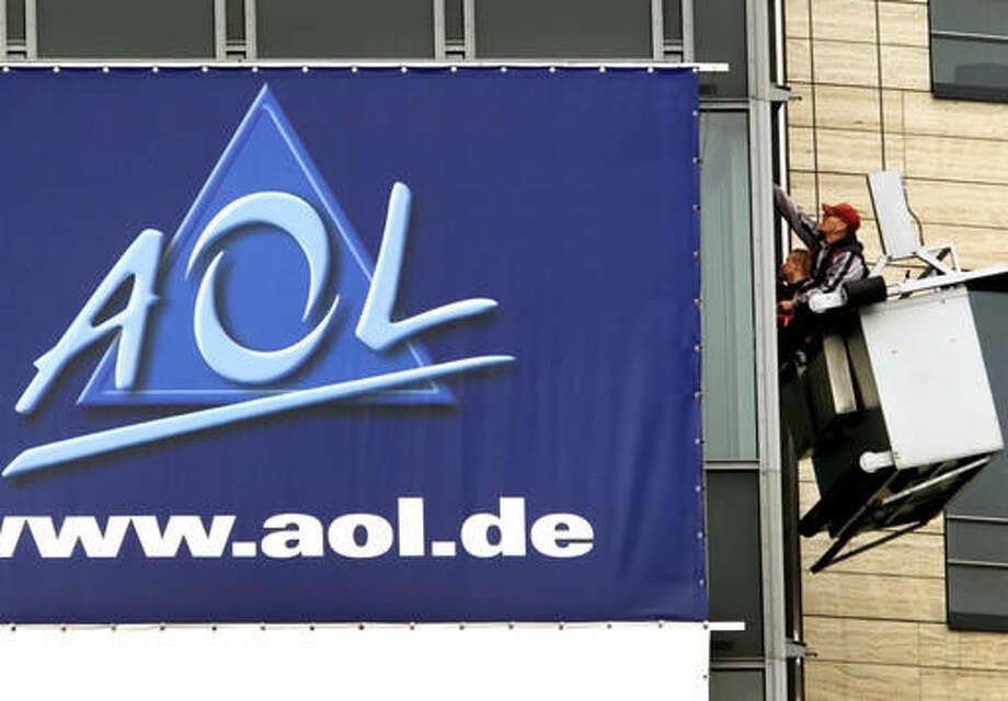 "FILE - In this March 17, 2000, file photo, window cleaners work at the front of the headquarters of AOL Europe in Hamburg, Germany. A California woman stumbled upon a voice from the past during a trip to Ohio over the weekend when she discovered her Uber driver was the man behind America Online's famous ""You've Got Mail"" greeting. Brandee Barker was in the Cleveland area to campaign for Hillary Clinton when she got into an Uber driven by Elwood Edwards. After Edwards told her about his claim to fame, she took a video of him saying the phrase and posted it on Twitter on Nov. 5, 2016. (AP Photo/Michael Probst, File)"