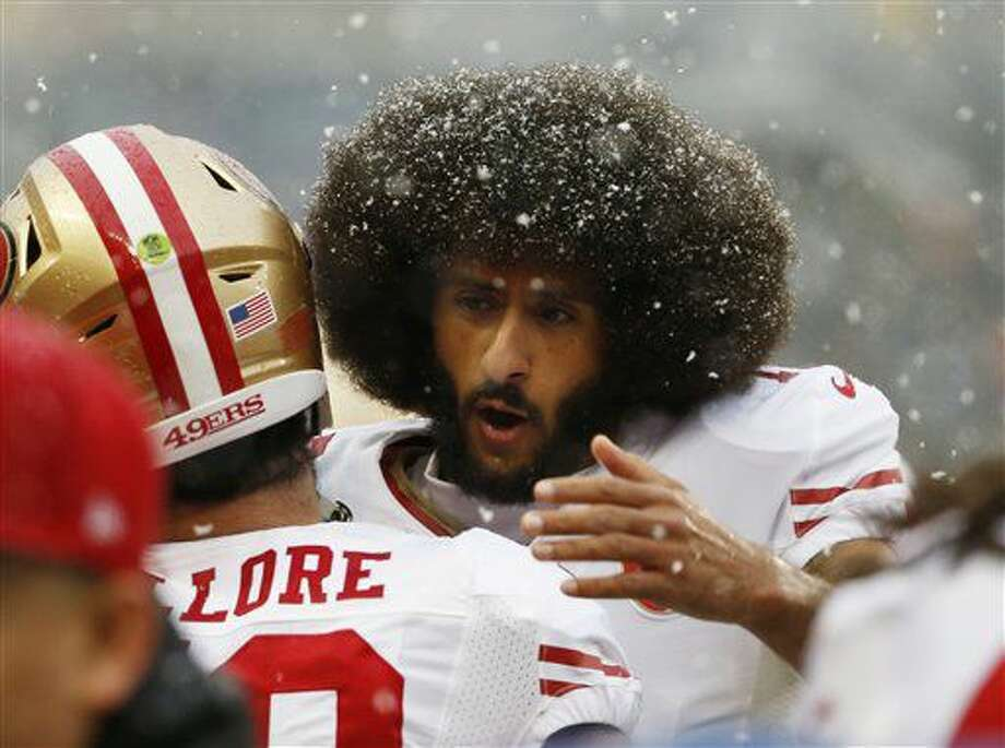 San Francisco 49ers quarterback Colin Kaepernick, right, hugs San Francisco 49ers linebacker Nick Bellore (50) before an NFL football game against the Chicago Bears, Sunday, Dec. 4, 2016, in Chicago. (AP Photo/Nam Y. Huh)