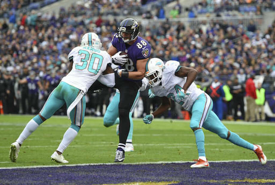 Baltimore Ravens tight end Dennis Pitta, center, scores a touchdown between Miami Dolphins free safety Bacarri Rambo, left, and strong safety Isa Abdul-Quddus in the first half of an NFL football game, Sunday, Dec. 4, 2016, in Baltimore. (AP Photo/Gail Burton)