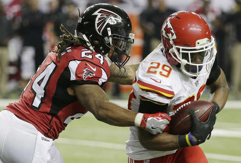 Kansas City Chiefs strong safety Eric Berry (29) breaks the tackle of Atlanta Falcons running back Devonta Freeman (24) after Berry made an interception during the first half of an NFL football game, Sunday, Dec. 4, 2016, in Atlanta. Berry scored a touchdown on the play(AP Photo/Chuck Burton)