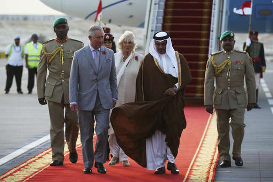 Britain's Prince Charles speaks to Bahrain's Crown Prince Salman bin Hamad bin Isa Al Khalifa upon arriving to Manama, Bahrain, on Tuesday, Nov. 8, 2016. Prince Charles and his wife Camilla, seen behind the two princes, are on a three-nation tour of the Gulf. (AP Photo/Jon Gambrell)