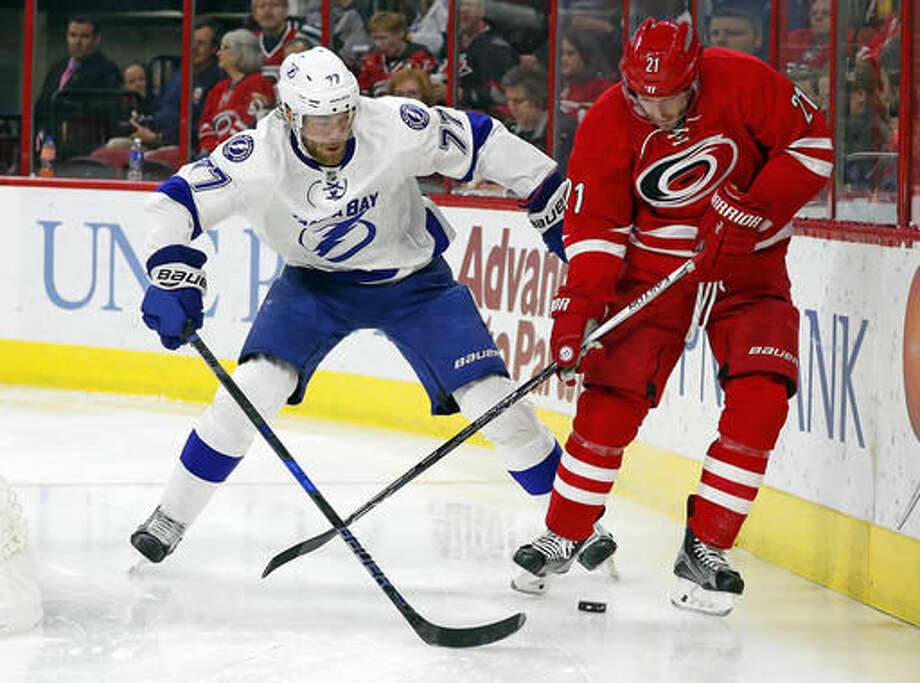 Carolina Hurricanes' Lee Stempniak (21) battles with Tampa Bay Lightning's Victor Hedman (77) during the second period of an NHL hockey game, Sunday, Dec. 4, 2016, in Raleigh, N.C. (AP Photo/Karl B DeBlaker)