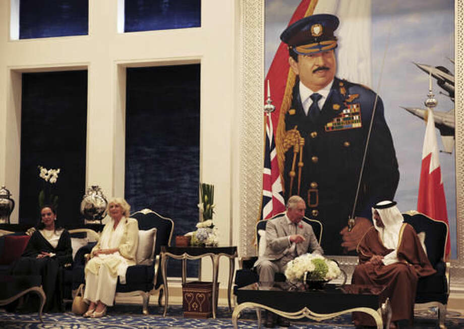 Britain's Prince Charles speaks to Bahrain's Crown Prince Salman bin Hamad bin Isa Al Khalifa, while his wife Camilla talks with Sheikh Hessa Al Khalifa in Manama, Bahrain, on Tuesday, Nov. 8, 2016. The British royal couple are on a three-nation tour of the Gulf. Bahrain's King Hamad bin Isa Al Khalifa is pictured in the painting behind them. (AP Photo/Jon Gambrell)