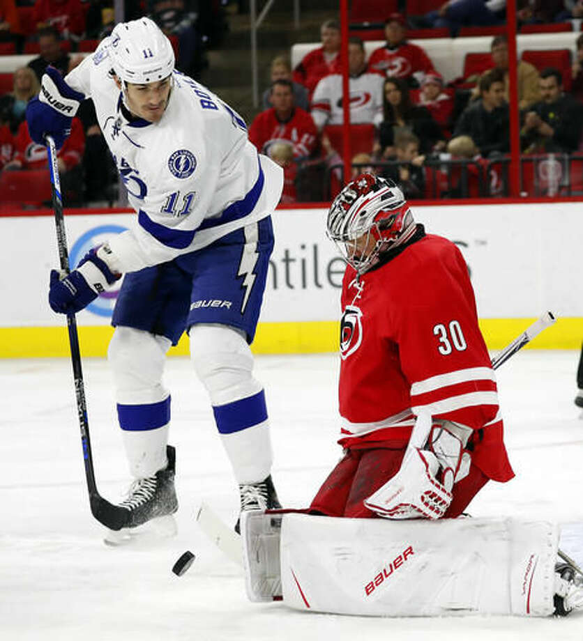 Carolina Hurricanes goalie Cam Ward (30) blocks a shot as Tampa Bay Lightning's Brian Boyle (11) looks for a rebound during the first period of an NHL hockey game, Sunday, Dec. 4, 2016, in Raleigh, N.C. (AP Photo/Karl B DeBlaker)