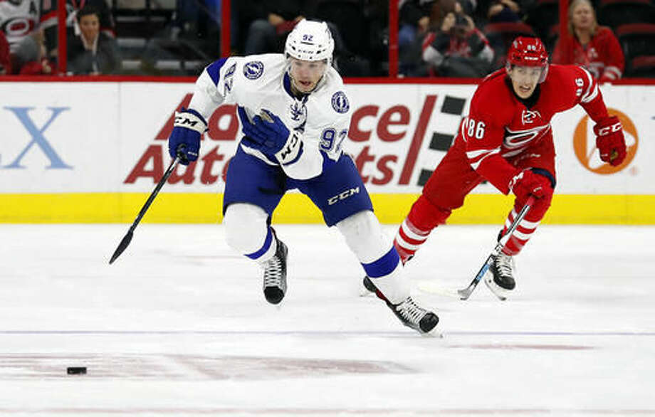 Tampa Bay Lightning's Joel Vermin (92) takes the puck down the ice after taking it away from Carolina Hurricanes' Teuvo Teravainen (86) during the first period of an NHL hockey game, Sunday, Dec. 4, 2016, in Raleigh, N.C. (AP Photo/Karl B DeBlaker)
