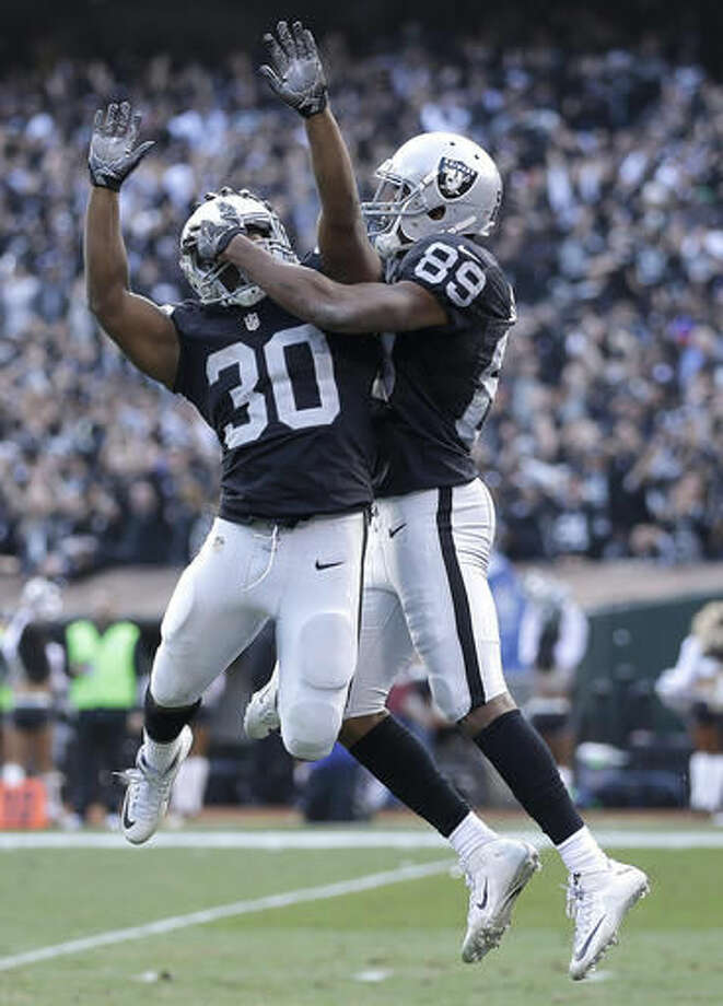 Oakland Raiders wide receiver Amari Cooper (89) celebrates after scoring a touchdown with running back Jalen Richard (30) during the second half of an NFL football game against the Buffalo Bills in Oakland, Calif., Sunday, Dec. 4, 2016. (AP Photo/Ben Margot)