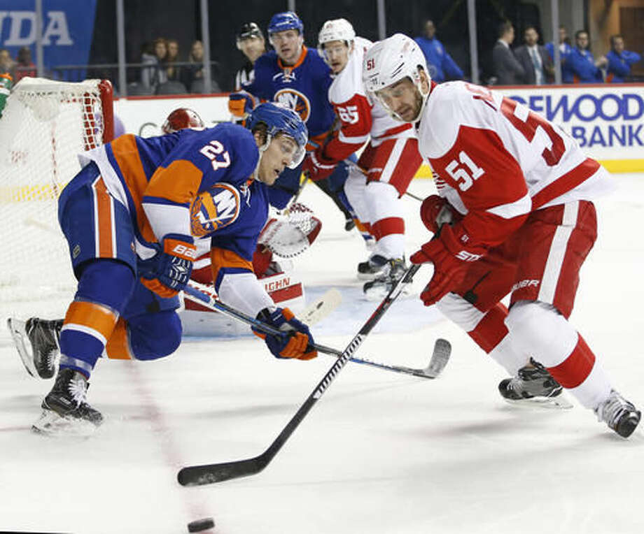 New York Islanders' left wing Anders Lee (27) loses his balance as Detroit Red Wings' center Frans Nielsen (51), of Denmark, takes control of the puck during the second period of an NHL hockey game, Sunday, Dec. 4, 2016, in New York. (AP Photo/Kathy Willens)