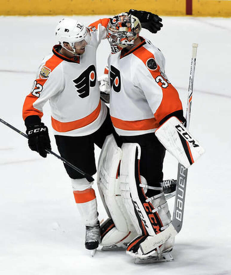 Philadelphia Flyers left wing Michael Raffl (12), of Austria, congratulates goalie Steve Mason (35) following the team's win against the Nashville Predators in an NHL hockey game Sunday, Dec. 4, 2016, in Nashville, Tenn. The Flyers won 4-2. (AP Photo/Mark Zaleski)