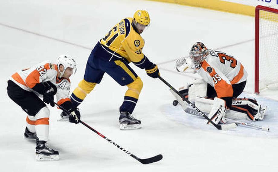 Philadelphia Flyers goalie Steve Mason (35) blocks a shot by Nashville Predators left wing Austin Watson (51) as defenseman Mark Streit (32), of Switzerland, looks for the rebound during the first period of an NHL hockey game, Sunday, Dec. 4, 2016, in Nashville, Tenn. (AP Photo/Mark Zaleski)