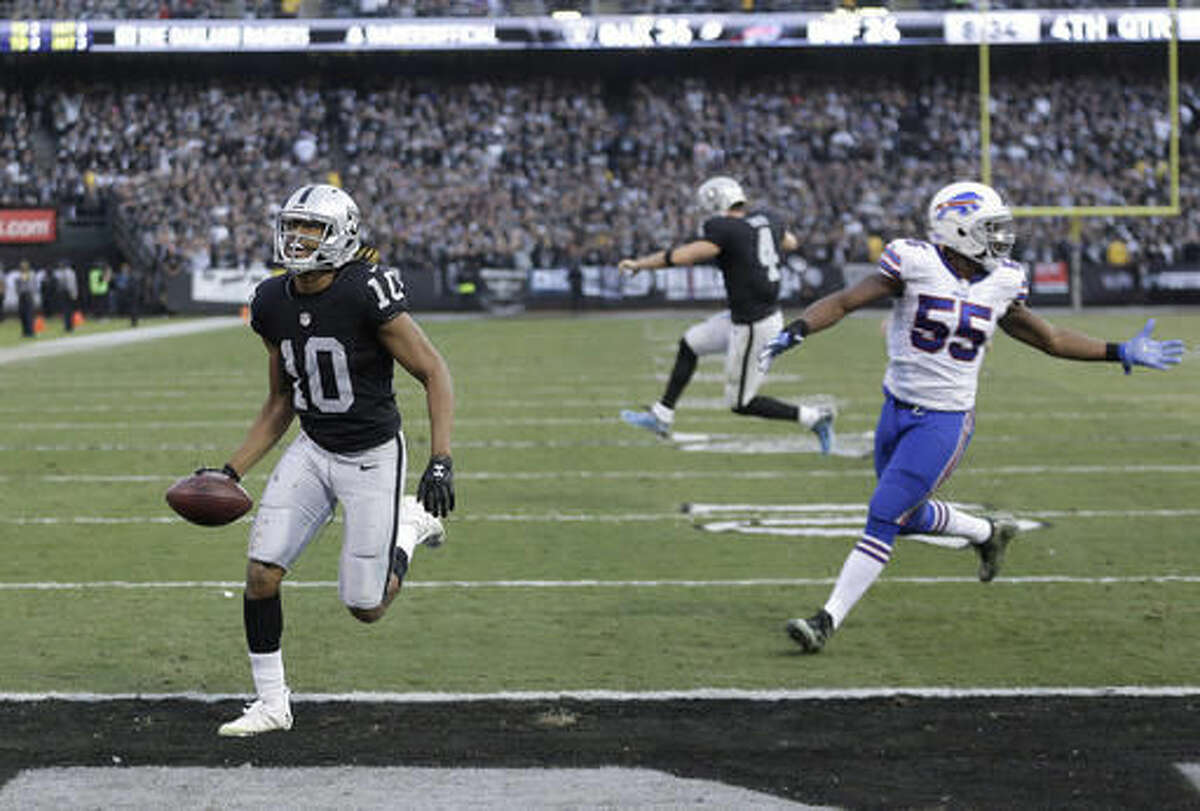Oakland Raiders wide receiver Seth Roberts (10) and quarterback Derek Carr, rear, celebrate after connecting on a two-point conversion against the Buffalo Bills during the second half of an NFL football game in Oakland, Calif., Sunday, Dec. 4, 2016. (AP Photo/Ben Margot)