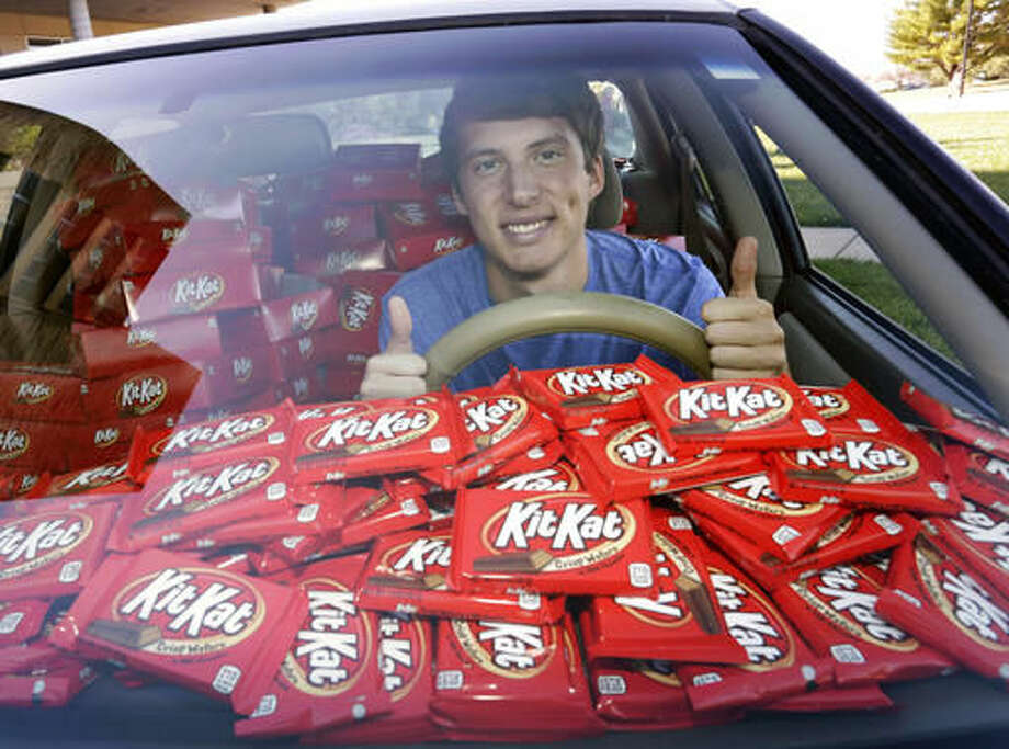 "In this Nov. 3, 2016, photo Hunter Jobbins, freshman at Kansas State University, poses in his car filled with nearly 6,500 Kit Kat bars in Manhattan, Kansas. Jobbins told The Wichita Eagle he left his car unlocked with a Kit Kat in the cupholder last month before running into his dorm building. When he came back, the candy bar had been replaced with a note. The thief wrote, ""I love Kit Kats so I checked your door and it was unlocked. Did not take anything other than the Kit Kat. I am sorry and hungry."" Jobbins' picture of the note went viral on Twitter and Hershey responded by sending a representative to the campus with 6,500 Kit Kat bars. (Colin E. Braley/AP Images for The Hershey Company)"