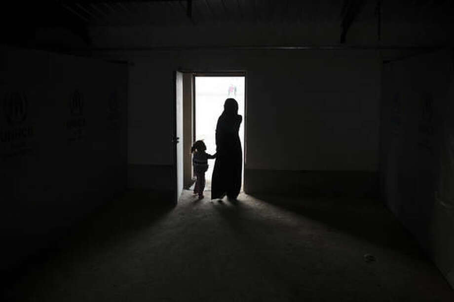 Iraqis displaced by fighting in Mosul walk out a building at a camp for internally displaced people in Hassan Sham, Iraq, on Tuesday, Nov. 8, 2016. The United Nations says over 34,000 people have been displaced from Mosul, with about three quarters settled in camps and the rest in host communities. (AP Photo/Felipe Dana)