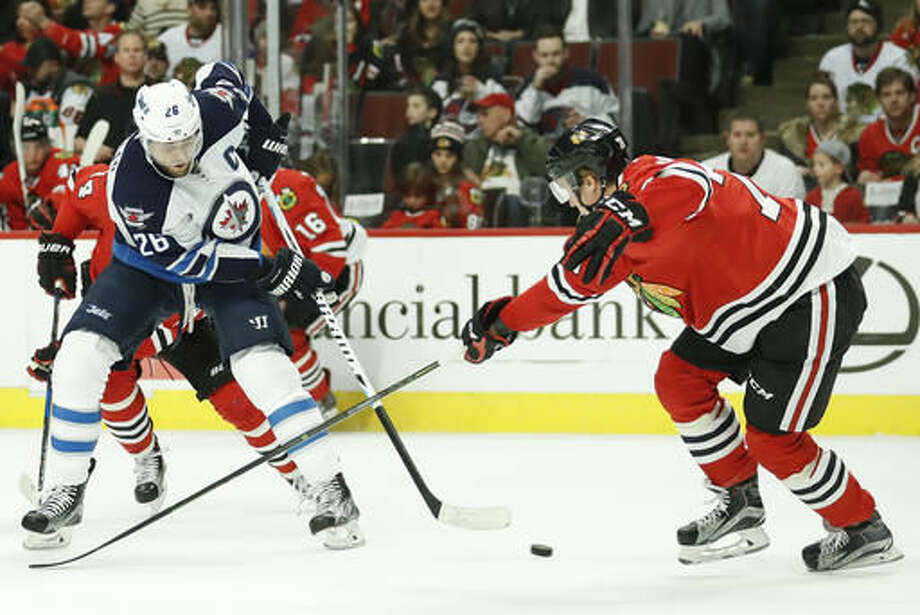 Winnipeg Jets right wing Blake Wheeler, left, tries to score against Chicago Blackhawks center Dennis Rasmussen, right, during the first period of an NHL hockey game Sunday, Dec. 4, 2016, in Chicago. (AP Photo/Kamil Krzaczynski)