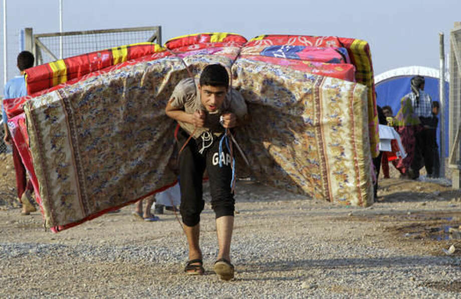 An Iraqi youth displaced by fighting in Mosul carries mattresses at a camp for internally displaced people in Khazer, Iraq, on Tuesday, Nov. 8, 2016. The United Nations says over 34,000 people have been displaced from Mosul, with about three quarters settled in camps and the rest in host communities. (AP Photo/Adam Schreck)