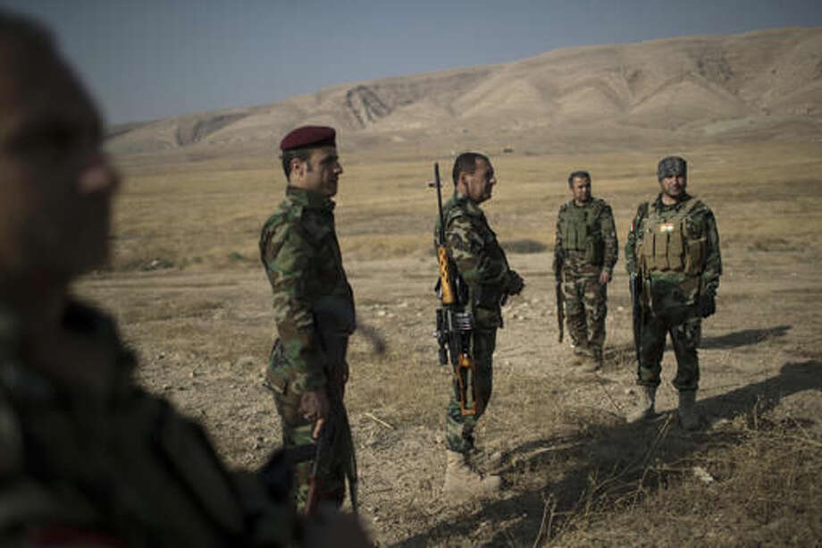 Kurdish Peshmerga fighters gather near a frontline during fighting with Islamic State militants in Bashiqa, east of Mosul, Iraq, Tuesday, Nov. 8, 2016. Iraqi troops and the Kurdish peshmerga forces are now converging on Mosul, although the deepest advance into an eastern sliver of the city has stalled after militants counterattacked advancing special forces from within built-up, populated areas. (AP Photo/Felipe Dana)