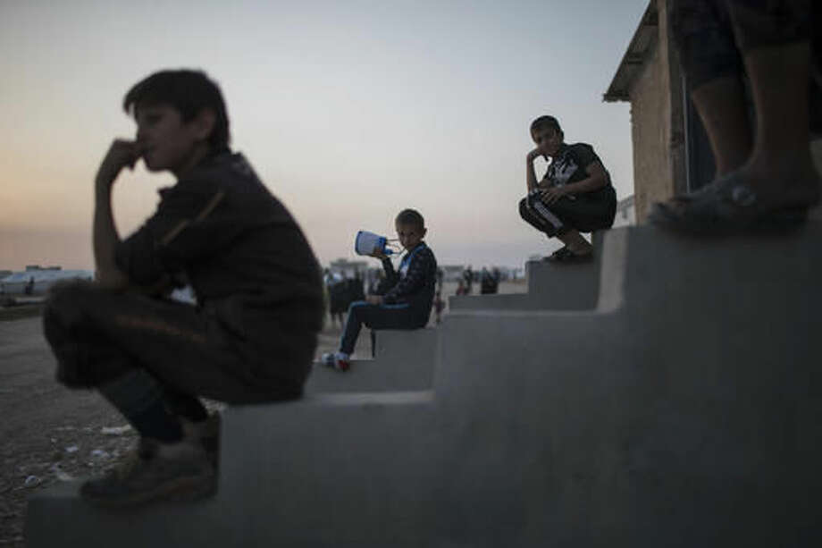 Iraqi boys displaced by fighting in Mosul sit at a camp for internally displaced people in Hassan Sham, Iraq, on Tuesday, Nov. 8, 2016. The United Nations says over 34,000 people have been displaced from Mosul, with about three quarters settled in camps and the rest in host communities. (AP Photo/Felipe Dana)