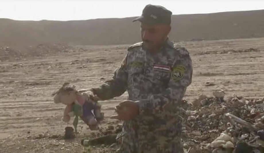 In this Monday, Nov. 7, 2016 frame grab from video, an Iraqi federal police officer holds a stuffed toy at the site of a mass grave in Hamam al-Alil, Iraq. Investigators are probing the mass grave that was discovered the previous day by troops advancing further into Islamic State-held territory near the city of Mosul. Associated Press footage from the site shows bones and decomposed bodies among scraps of clothing and plastic bags dug out of the ground by a bulldozer after Iraqi troops noticed the strong smell while advancing into the town of Hamam al-Alil. (AP Photo)