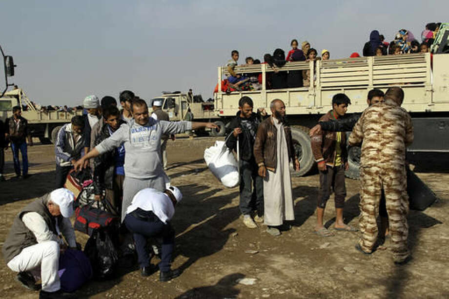 Iraqi men displaced by fighting in Mosul are searched before being allowed into a camp for internally displaced people in Khazer, Iraq, on Tuesday, Nov. 8, 2016. The United Nations says over 34,000 people have been displaced from Mosul, with about three quarters settled in camps and the rest in host communities. (AP Photo/Adam Schreck)