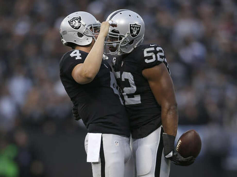 Oakland Raiders quarterback Derek Carr (4) celebrates with defensive end Khalil Mack (52) during the second half of an NFL football game against the Buffalo Bills in Oakland, Calif., Sunday, Dec. 4, 2016. The Raiders won 38-24. (AP Photo/D. Ross Cameron)