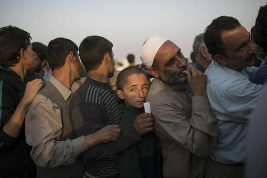 Iraqis displaced by fighting in Mosul line up for food distribution at a camp for internally displaced people in Hassan Sham, Iraq, on Tuesday, Nov. 8, 2016. The United Nations says over 34,000 people have been displaced from Mosul, with about three quarters settled in camps and the rest in host communities. (AP Photo/Felipe Dana)