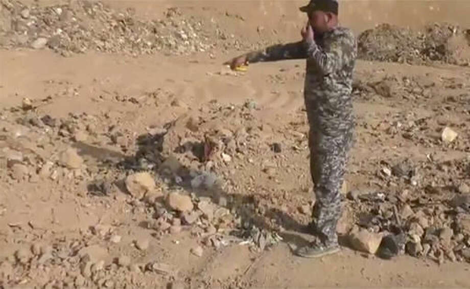 In this Monday, Nov. 7, 2016 frame grab from video, an Iraqi federal police officer holds his nose as he points towards a mass grave in Hamam al-Alil, Iraq. Investigators are probing the mass grave that was discovered the previous day by troops advancing further into Islamic State-held territory near the city of Mosul. Associated Press footage from the site shows bones and decomposed bodies among scraps of clothing and plastic bags dug out of the ground by a bulldozer after Iraqi troops noticed the strong smell while advancing into the town of Hamam al-Alil. (AP Photo)
