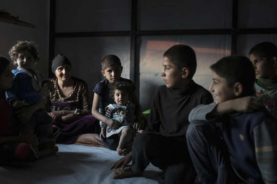 Iraqis displaced by fighting in Mosul sit inside a tent at a camp for internally displaced people in Hassan Sham, Iraq, on Tuesday, Nov. 8, 2016. The United Nations says over 34,000 people have been displaced from Mosul, with about three quarters settled in camps and the rest in host communities. (AP Photo/Felipe Dana)