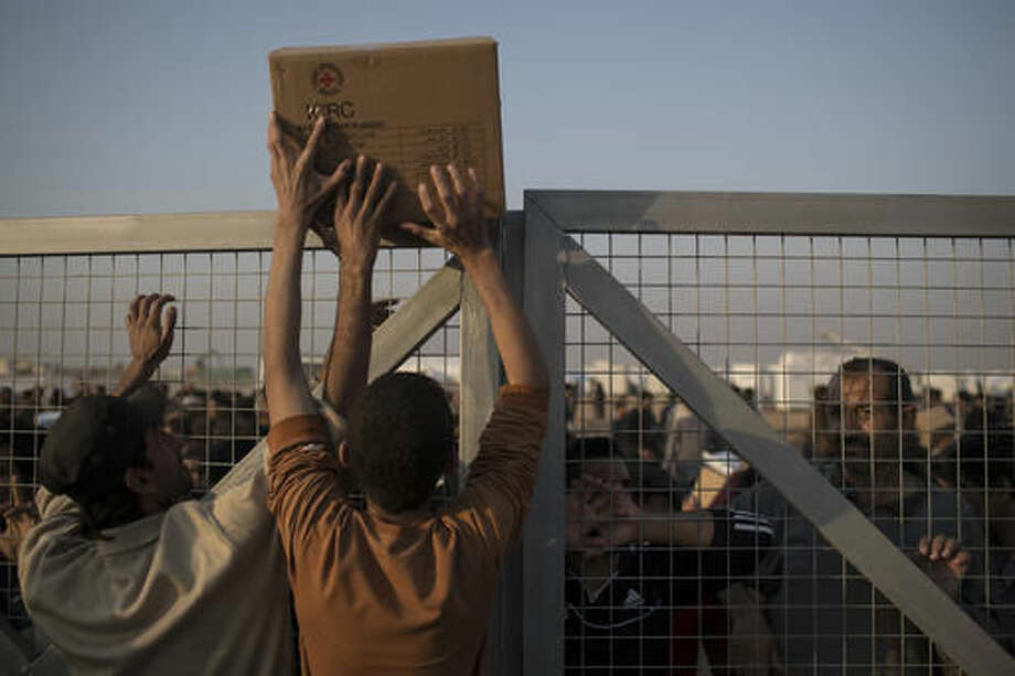Iraqis displaced by fighting in Mosul pass food supplies over a fence at a camp for internally displaced people in Hassan Sham, Iraq, on Tuesday, Nov. 8, 2016. The United Nations says over 34,000 people have been displaced from Mosul, with about three quarters settled in camps and the rest in host communities. (AP Photo/Felipe Dana)