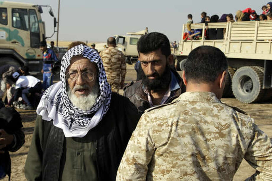 Iraqi men fleeing fighting in Mosul enter a camp for internally displaced people in Khazer, Iraq, after being searched on Tuesday, Nov. 8, 2016. The United Nations says over 34,000 people have been displaced from Mosul, with about three quarters settled in camps and the rest in host communities. (AP Photo/Adam Schreck)