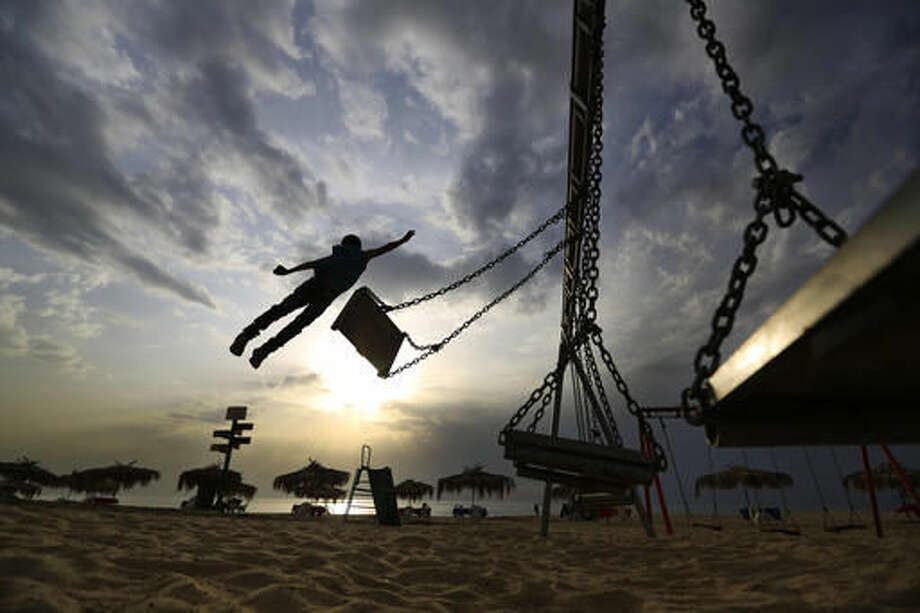 Syrian refugee Mohammed Assaf, 9, jumps from a swing at the public beach of Ramlet al-BaIda in Beirut, Lebanon.  Photo: Hassan Ammar