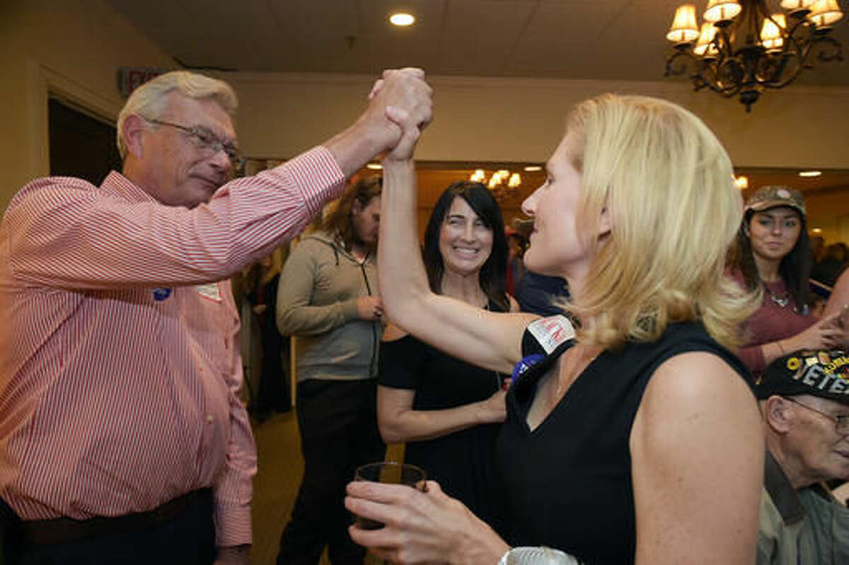 Williamson County Republican Party chairman Julie Hannah,right, high fives a Trump supporter during a Williamson County Republican watch party on election night at Old Natchez Country Club in Franklin, Tenn. on Tuesday, Nov. 8, 2016. (Shelley Mays/The Tennessean via AP)