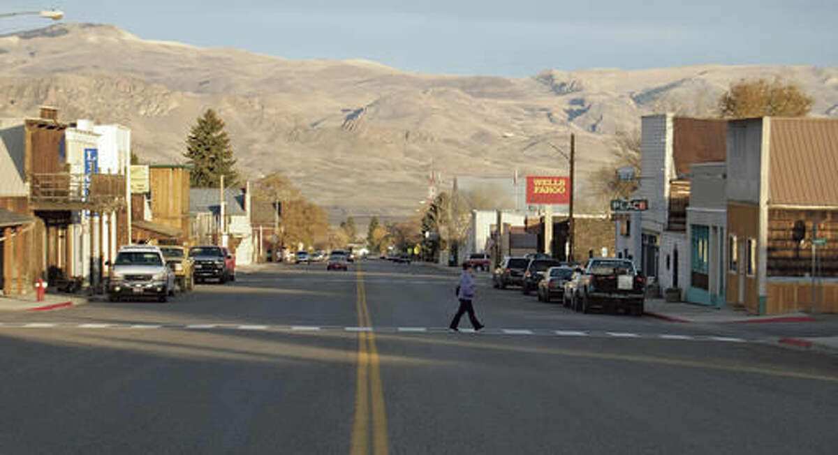 In this Nov. 7, 2016 photo, a woman crosses a street in Challis, Idaho. Challis, population 1,000, is surrounded by hundreds of thousands of acres of public lands. With a recent fire at the Bureau of Land Management offices in Challis, central Idaho federal employees are returning to work with local help. (Luke Ramseth/Post Register via AP)