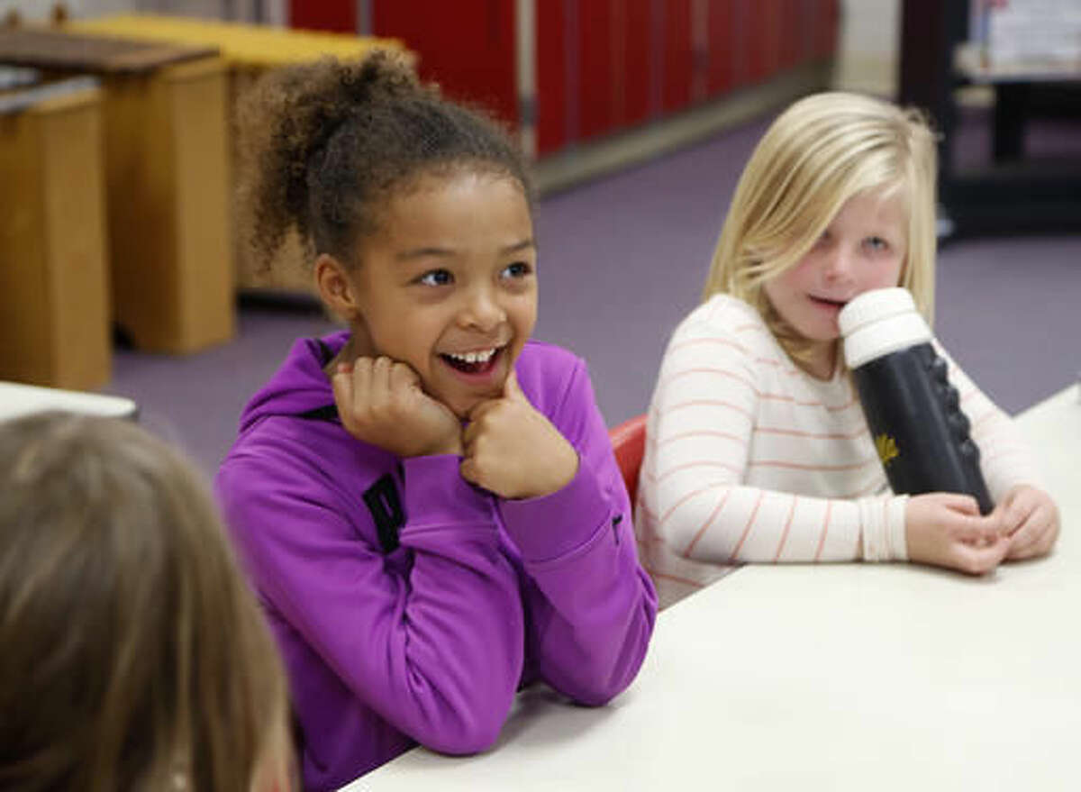 In this Tuesday, Nov. 8, 2016 photo, Amalia Djoumessi, left, talks about her favorite TV character during their IMpower after-school program at Margaretta Carey Elementary School, in Waverly, Iowa. (Matthew Putney /The Courier via AP)