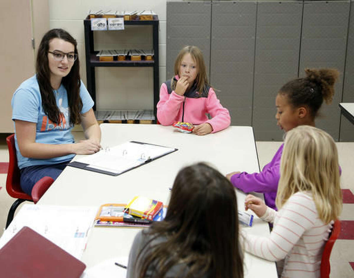 In this Tuesday, Nov. 8, 2016 photo, teacher Gabrielle Calease Fox, left, talks with Millie Helgevold, Amalia Djoumessi, Sydni Heims and Lauren Dohnen about positive images of yourself at IMpower after-school program at Margaretta Carey Elementary School in Waverly, Iowa. (Matthew Putney/The Courier via AP)