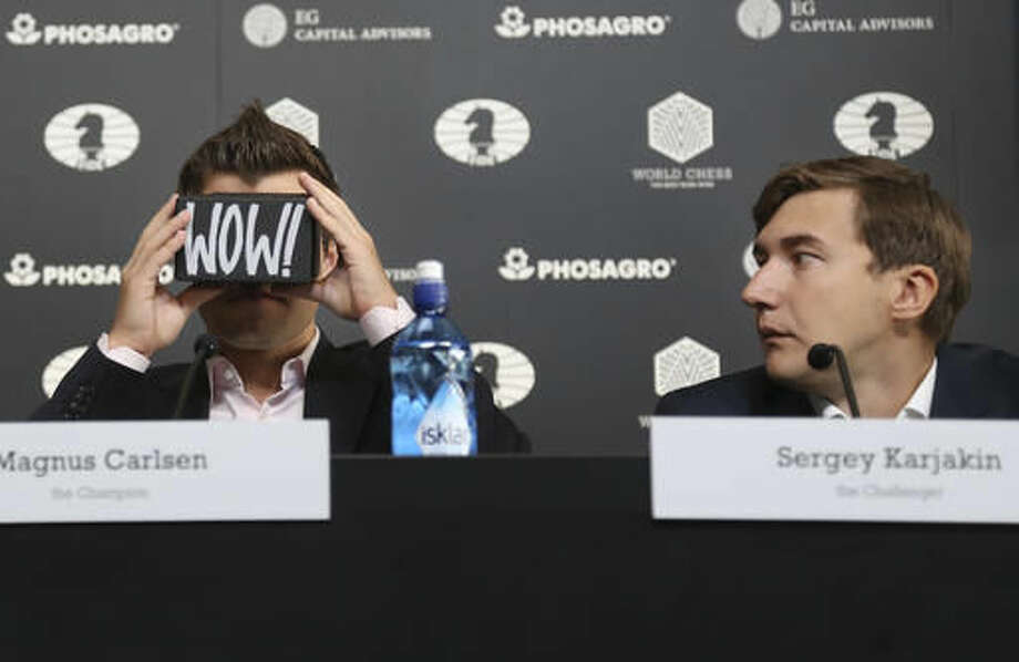 Chess world champion Magnus Carlsen, of Norway, left, looks through a virtual reality viewer while his challenger, Sergey Karjakin, of Russia, looks on during a news conference to promote the World Chess Championship in New York, Thursday, Nov. 10, 2016. The championship, which will also be broadcast live in 360 degrees, starts Nov. 11, 2016, in New York. (AP Photo/Seth Wenig) Photo: Seth Wenig