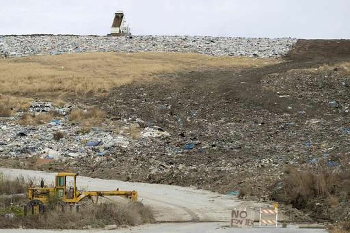 A truck dumps dirt onto trash at the Sarpy County landfill Thursday Nov 17, 2016, in Springfield, Neb. Officials say Sarpy County's 160-acre landfill is finally shutting down after past closure dates have come and gone. It is likely to be closed in the fall of 2017 by being capped with dirt and grass. (Ryan Soderlin//Omaha World-Herald via AP)