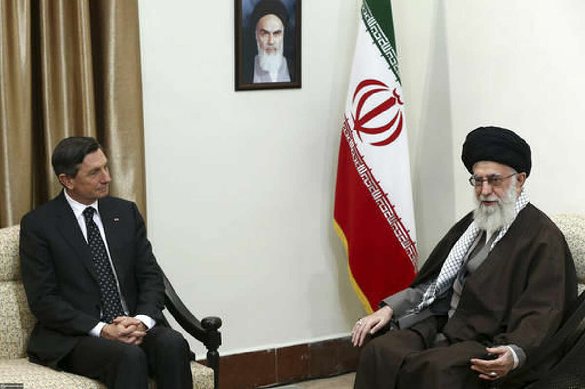 In this picture released by an official website of the office of the Iranian supreme leader, Supreme Leader Ayatollah Ali Khamenei, right, talks with Slovenian President Borut Pahor in their meeting in Tehran, Iran, Tuesday, Nov. 22, 2016. A portrait of the late Iranian revolutionary founder Ayatollah Khomeini hangs on the wall. (Office of the Iranian Supreme Leader via AP)