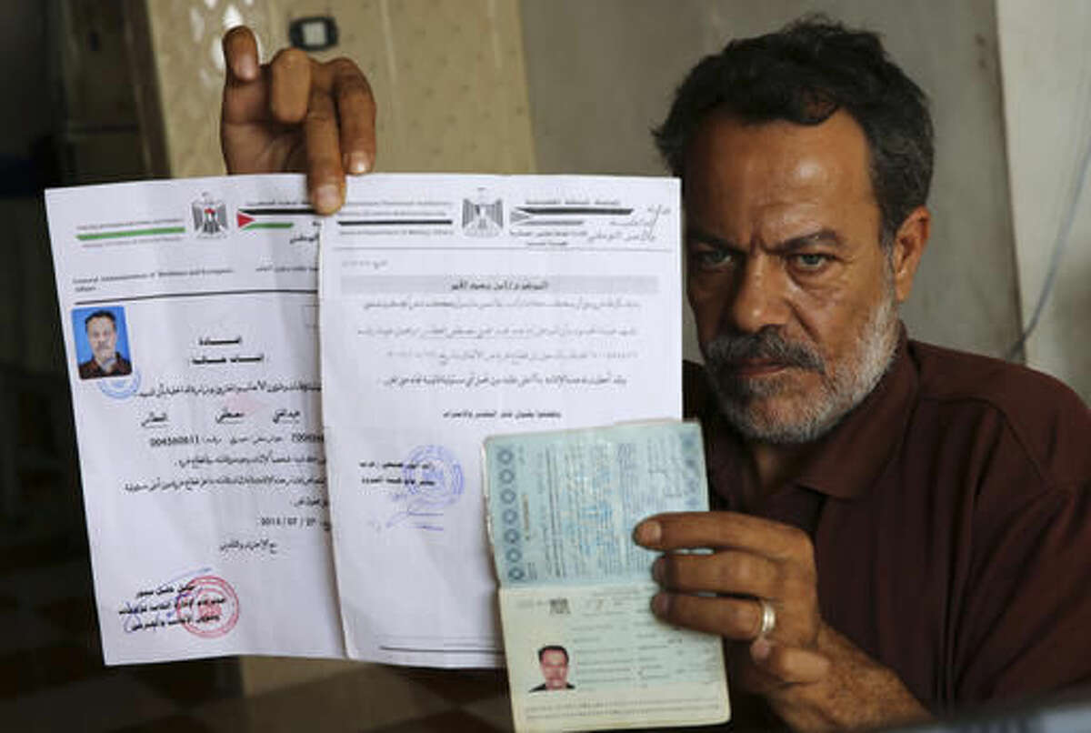 In this Oct. 31, 2016 photo, Syrian refugee, Majed al-Attar, poses while showing his expired Syrian passport and Palestinian identification documents at his family's rented house in Rafah, Gaza. Like millions of Syrians, the al-Attar family fled the civil war in his homeland in search of safety and security, but in a decision they now regret, they chose to go to Gaza. The al-Attar family is among 12 Syrian households that found refuge in Gaza after the civil war erupted in 2011 and are now trapped in the war-battered territory, but also unable to travel abroad. (AP Photo/Adel Hana)