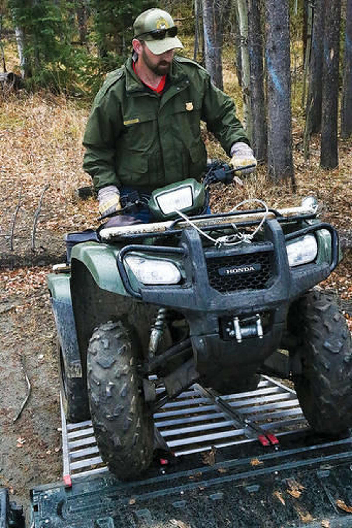 In this Oct. 29, 2016 photo, Wyoming Game and Fish Senior Game Warden Bill Brinegar drives an ATV up a ramp into the bed of a pickup truck in Laramie, Wyo. While his jurisdiction is statewide, Brinegar said he spends most of his time in the South Laramie Game Warden District. Instead of working in shifts, he said he is on call 24 hours a day, seven days a week. (Ike Fredregill/Laramie Boomerang via AP)