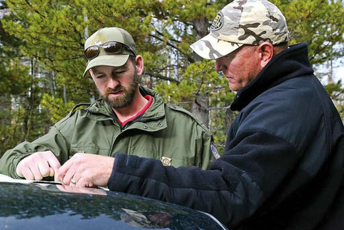 In this Oct. 29, 2016 photo, Wyoming Game and Fish Senior Game Warden Bill Brinegar, left, shows Tom Gabriel where to hunt elk in the area on a map in Laramie, Wyo. Brinegar said he spends most of his time in the South Laramie Game Warden District. Instead of working in shifts, he said he is on call 24 hours a day, seven days a week. (Ike Fredregill/Laramie Boomerang via AP)