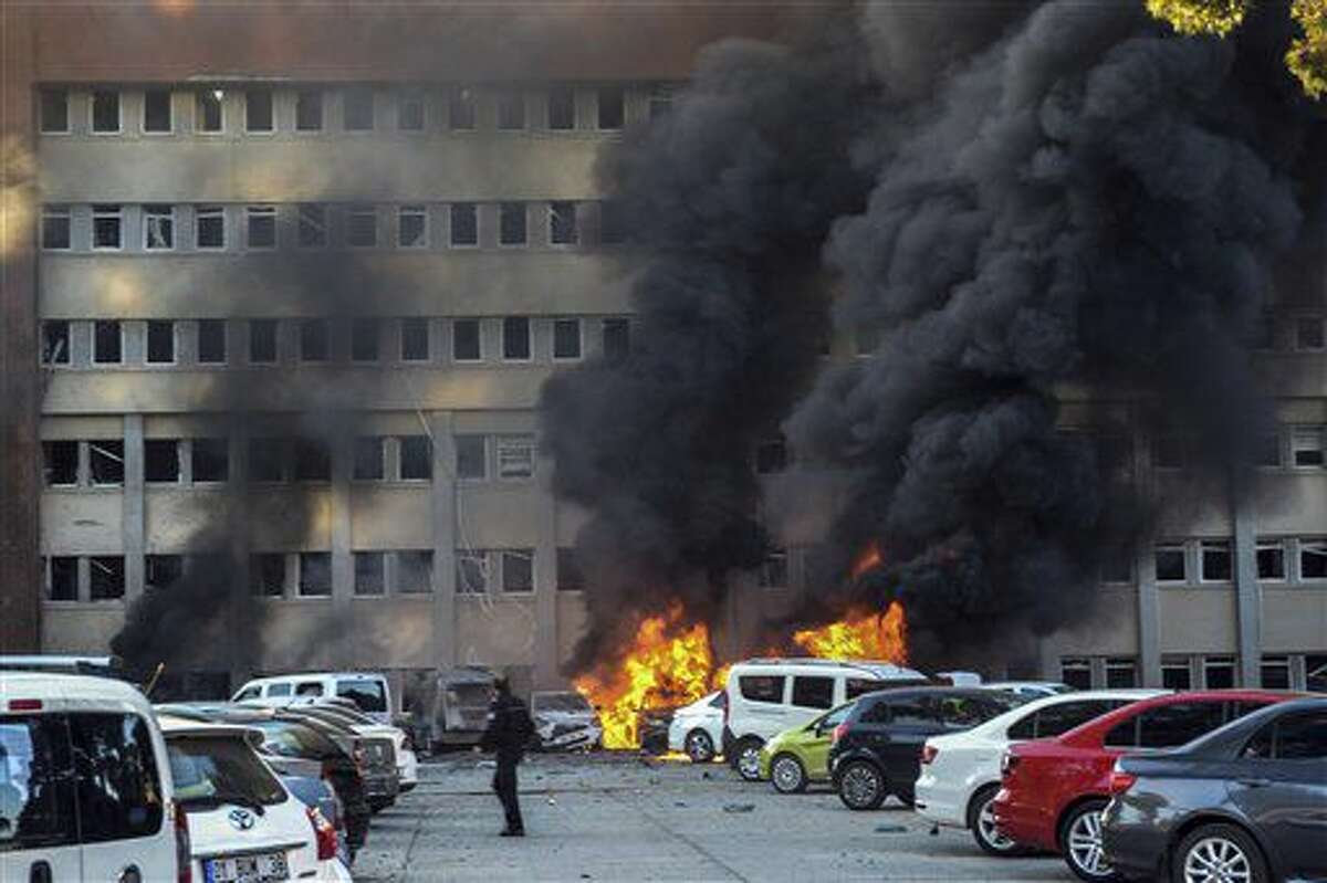 A police officer walks past by a fire after an explosion that killed people and wounded several others in southern city of Adana, Turkey, Thursday, Nov. 24, 2016. The explosion occurred early Thursday in the car park of a government building, officials said. Turkish authorities have banned distribution of images relating to the Adana explosion within Turkey. (AP Photo)