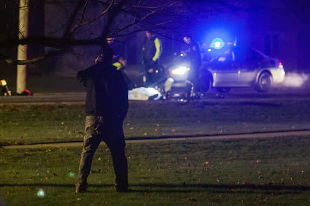 A bystander watches investigators at the scene of a fatal hit and run involving a cyclist on Mapleridge Road near Sunnyview Drive in Carrollton Township that occurred Sunday evening, Nov. 27, 2016. (Josie Norris /The Saginaw News via AP)
