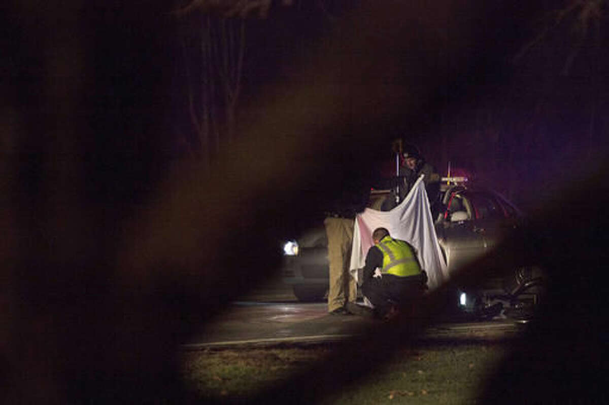 Police investigate the scene of a fatal hit and run involving a cyclist on Mapleridge Road near Sunnyview Drive in Carrollton Township that occurred Sunday evening, Nov. 27, 2016. (Josie Norris /The Saginaw News via AP)