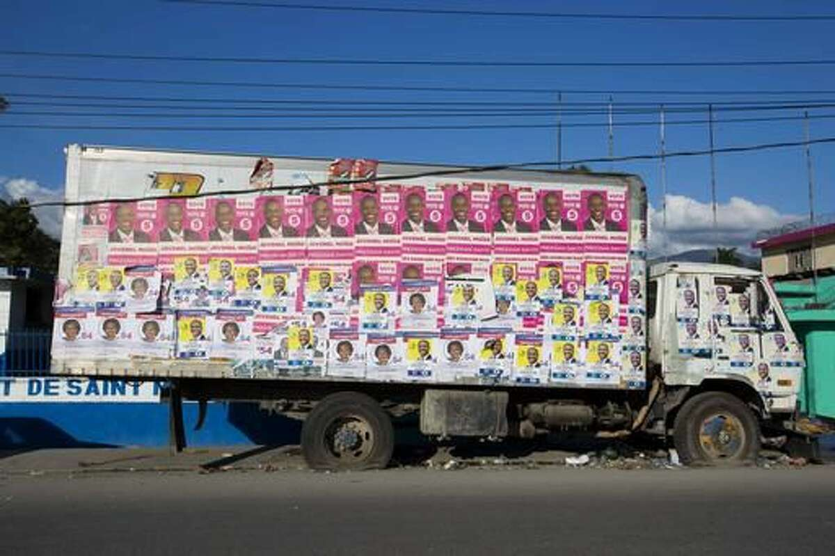 This Wednesday, Nov. 16, 2016 photo shows an abandoned truck plastered with campaign posters of several presidential candidates, in Arcahaie, Haiti. Haitians will try yet again to elect a president Sunday despite the fact that much of the southwest is still in ruins from Hurricane Matthew, parts of the north have been battered by floods and the country remains in political disarray. (AP Photo/Dieu Nalio Chery)