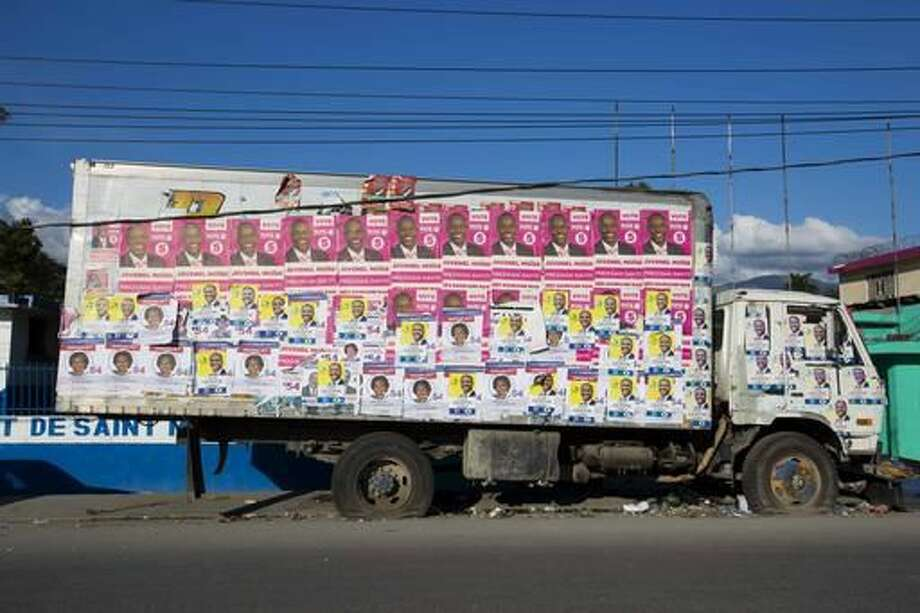 This Wednesday, Nov. 16, 2016 photo shows an abandoned truck plastered with campaign posters of several presidential candidates, in Arcahaie, Haiti. Haitians will try yet again to elect a president Sunday despite the fact that much of the southwest is still in ruins from Hurricane Matthew, parts of the north have been battered by floods and the country remains in political disarray. (AP Photo/Dieu Nalio Chery) Photo: Dieu Nalio Chery