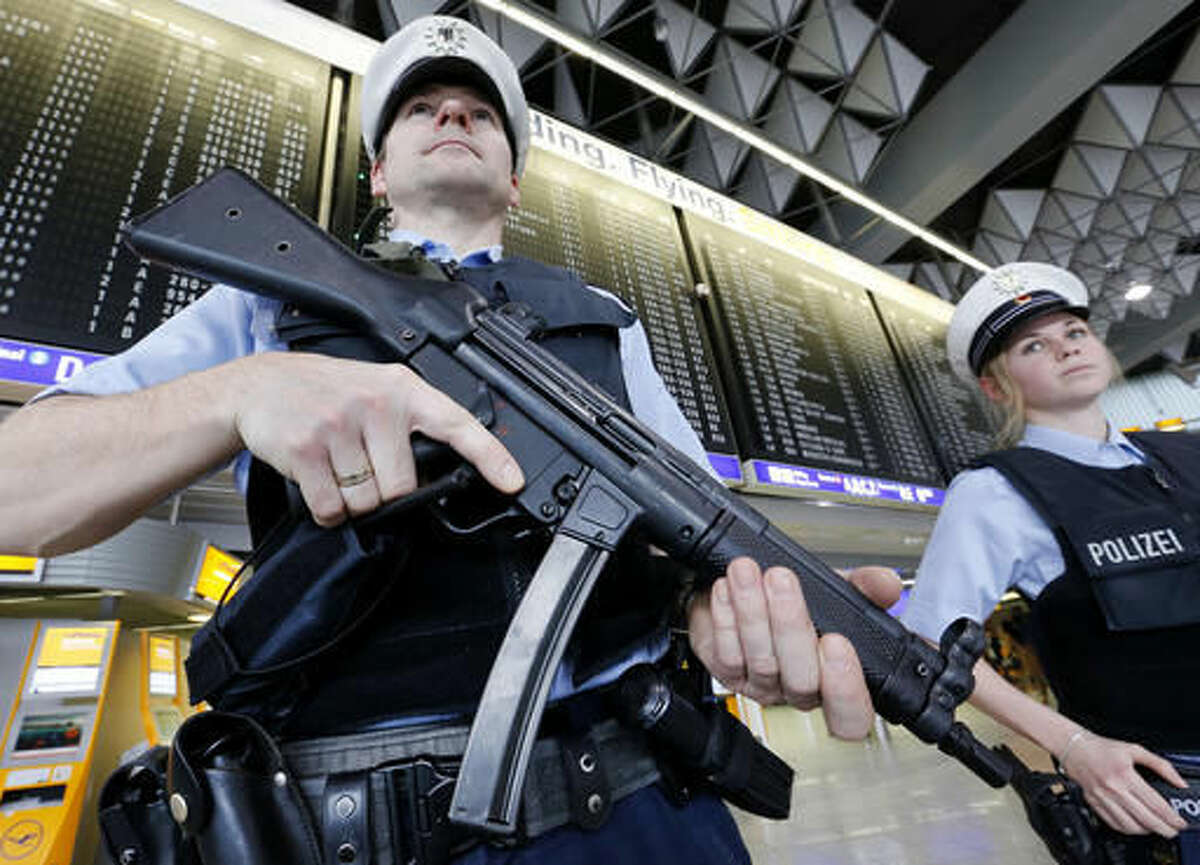 FILE - In this March 23, 2016 file photo, German police officers guard a terminal at the airport in Frankfurt, Germany, after security measures were increased after the Belgium attacks the previous day. The European Union unveiled plans on Wednesday, Nov. 16, 2016, for a new system of security checks on travelers permitted to enter Europe without visas in an effort to crack down on extremists. (AP Photo/Michael Probst, File)